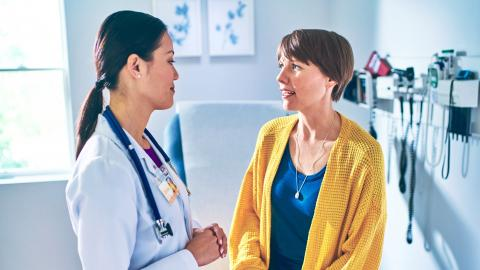 A woman sits on an examination table in a doctor's office, and speaks to a female doctor in a white coat with a stethoscope around her neck.