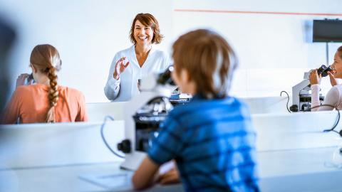 Teacher and students in classroom with microscopes