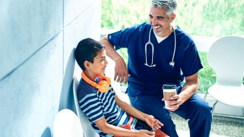 Physician and young boy talking in waiting room.