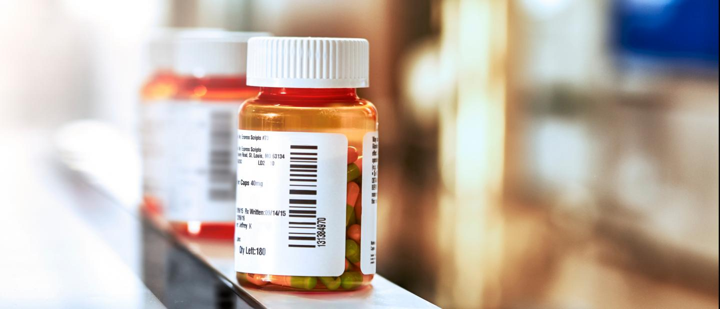 Pill bottle is lined up on a counter, with other pill bottles blurred in the background.