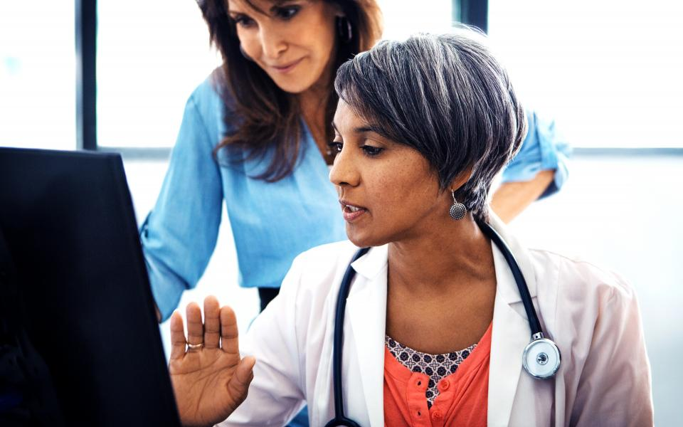 A female doctor wearing a lab coat and stethoscope looks at information on a screen, as another woman looks at the screen over her shoulder.