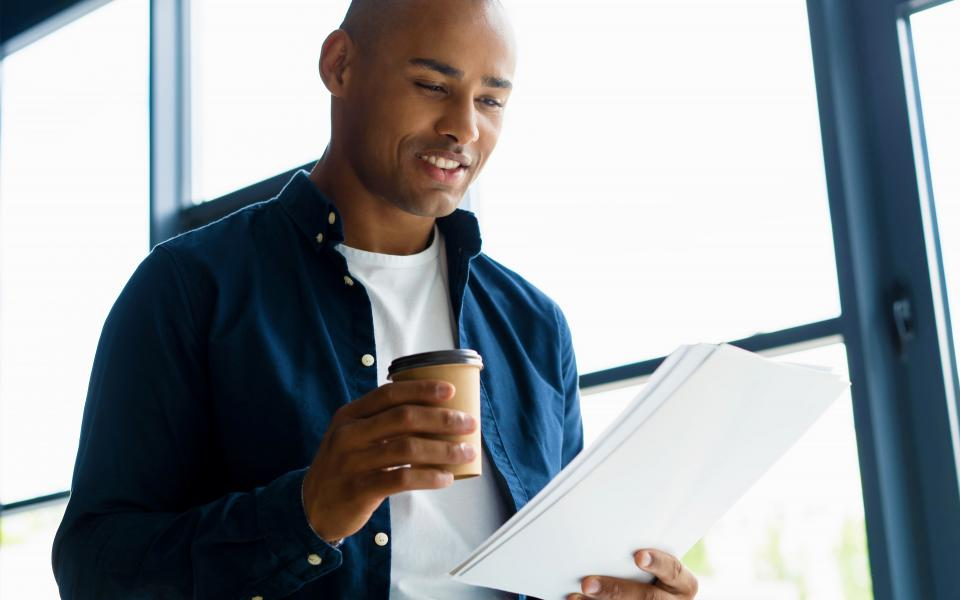 A man holds a cup of coffee in front of a bright window and reads a stack of papers.