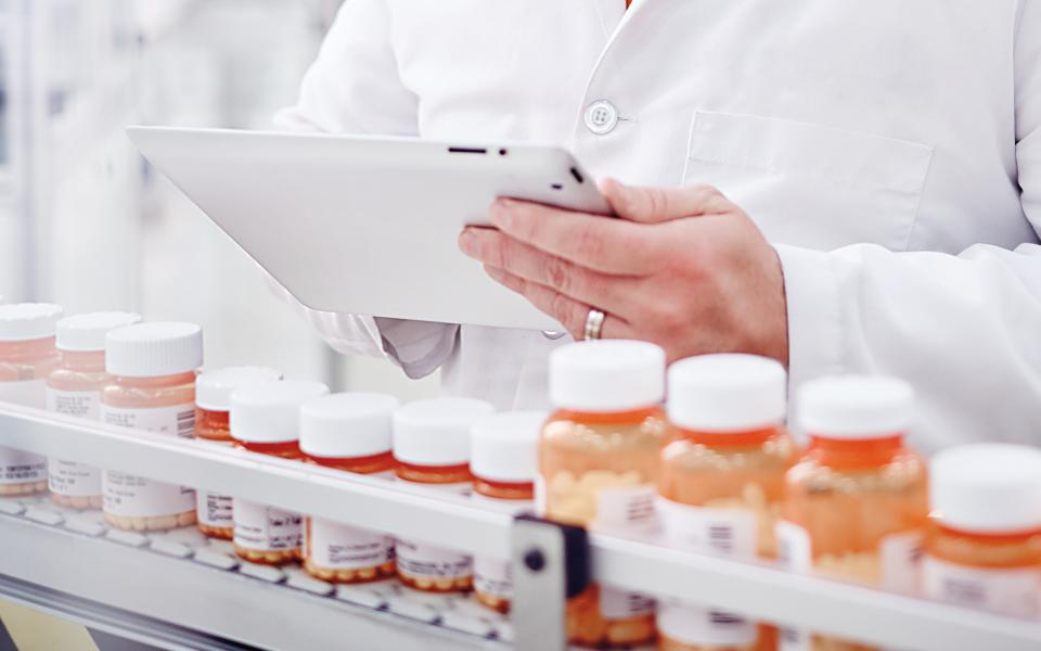 Person in lab coat holding a tablet device, looking over a row of pill bottles in a pharmacy.