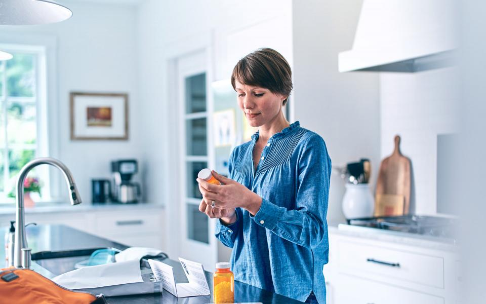 Woman in kitchen with pill bottle in hand