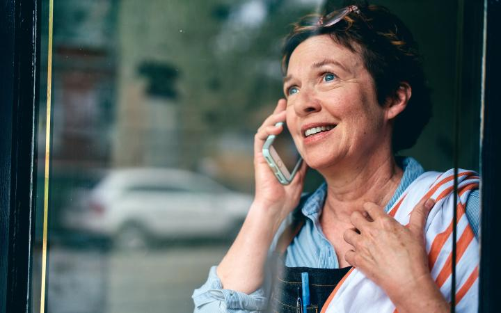 Patient smiling on the phone with Express Scripts customer service.