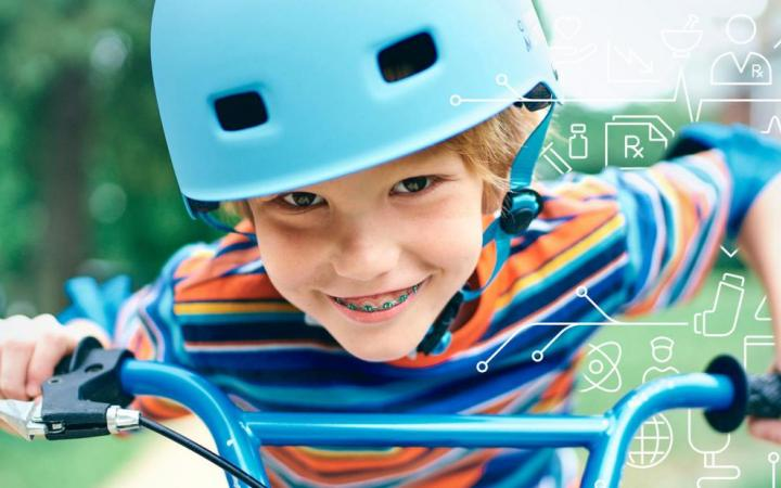 Young boy with braces sits on a bike with a light blue helment on, smiling at the camera.