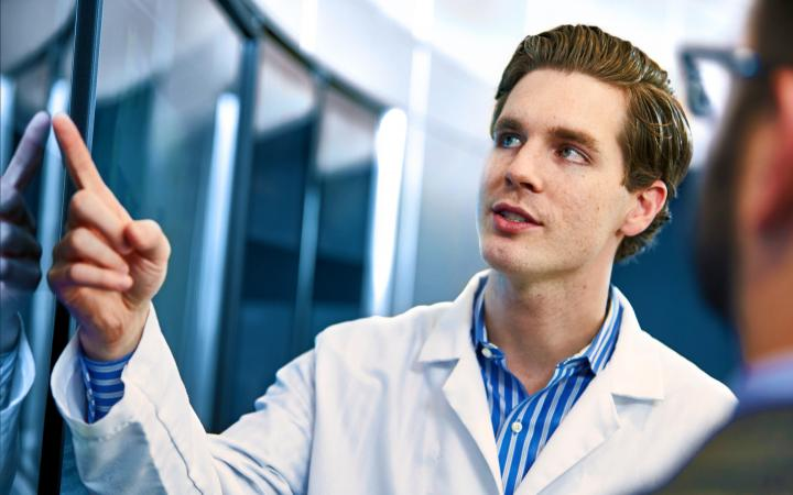 Man in a lab coat speaks to another person as he points to a screen.