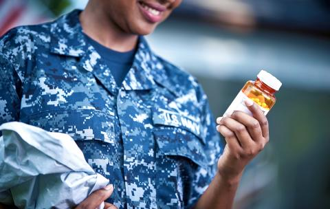 A woman in a US Navy uniform smiles as she reads the label on a pill bottle in her hands.